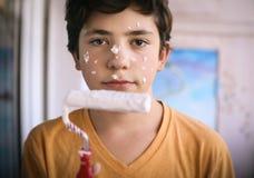 El muchacho sonriente del adolescente con el rodillo de pintura blanco y la cara sucia hacen para repintar Imagenes de archivo