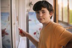 El muchacho sonriente del adolescente con el rodillo de pintura blanco y la cara sucia hacen para repintar Fotos de archivo libres de regalías