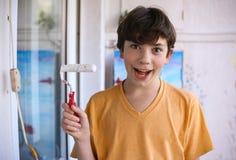 El muchacho sonriente del adolescente con el rodillo de pintura blanco y la cara sucia hacen para repintar Imagen de archivo