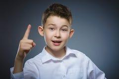 El muchacho sonriente del preadolescente con buena idea sostiene el finger para arriba aislado en fondo gris fotos de archivo libres de regalías