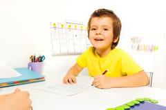 El muchacho sonriente dibuja con el lápiz en el papel Fotos de archivo libres de regalías