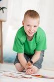 El muchacho sonriente en camisa y mezclilla verdes pone en cortocircuito las pinturas Fotografía de archivo libre de regalías