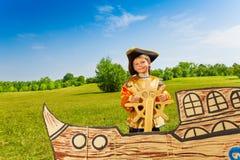 El muchacho sonriente en traje del pirata sostiene el timón Imagenes de archivo