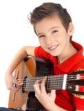 El muchacho sonriente está jugando en la guitarra acústica Imágenes de archivo libres de regalías