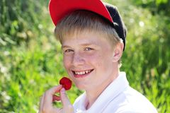 El muchacho sonriente está llevando el casquillo rojo que come la fresa Foto de archivo libre de regalías