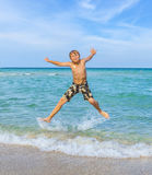 El muchacho sonriente está saltando en el aire en una playa tropical Imagenes de archivo
