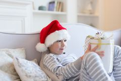 El muchacho sonriente feliz en el sombrero rojo de Papá Noel se sienta en el sofá que sostiene la actual caja Foto interior La Na imagen de archivo