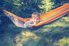 El muchacho sonriente lindo está balanceando en una hamaca en un claro del bosque Imagen de archivo
