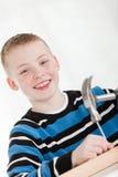 El muchacho sonriente martilla el clavo en el pedazo de madera Imágenes de archivo libres de regalías