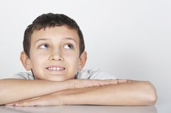 El muchacho sonriente mira cuidadosamente hacia arriba Imagen de archivo