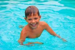 El muchacho sonriente nada en piscina foto de archivo