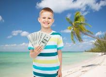 El muchacho sonriente que lleva a cabo el dólar cobra el dinero en su mano Foto de archivo
