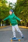 El muchacho sonriente que se coloca en penique plástico del color sube Imagen de archivo libre de regalías