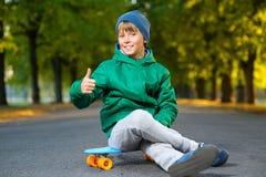 El muchacho sonriente que se sienta en penique plástico del color sube Fotos de archivo