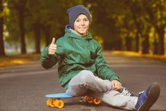 El muchacho sonriente que se sienta en penique plástico del color sube Fotos de archivo libres de regalías