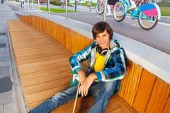 El muchacho sonriente se sienta con el brazo en rodilla sostiene el monopatín Foto de archivo libre de regalías