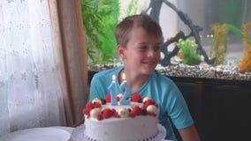 El muchacho sopla hacia fuera las velas en la torta en cumpleaños almacen de metraje de vídeo