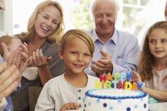 El muchacho sopla hacia fuera velas de la torta de cumpleaños en el partido de la familia Imágenes de archivo libres de regalías