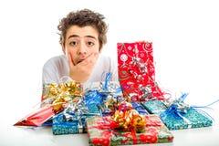 El muchacho sorprendente se sostiene la barbilla mientras que recibe los regalos de la Navidad Imagen de archivo