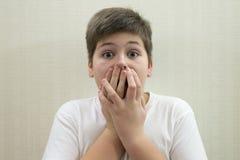 El muchacho sorprendido cierra la boca con las manos imagenes de archivo