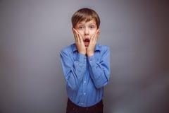 El muchacho sorprendido del adolescente abrió su boca en gris Imagen de archivo libre de regalías