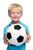 El muchacho sostiene el balón de fútbol Imagenes de archivo