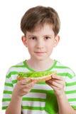 El muchacho sostiene el pan blanco con la ensalada verde Fotos de archivo libres de regalías