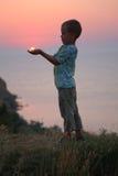 El muchacho sostiene el sol en manos foto de archivo libre de regalías