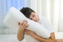 El muchacho sostiene en sus manos la almohada anatómica que se sienta en cama Foto de archivo libre de regalías