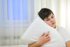 El muchacho sostiene en sus manos la almohada anatómica que se sienta en cama Fotografía de archivo libre de regalías