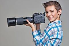 El muchacho sostiene la cámara grande de la foto Fotos de archivo