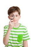 El muchacho sostiene la lupa enfrente de su ojo Imagen de archivo