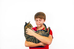 El muchacho sostiene su gato de gato atigrado en sus brazos Imágenes de archivo libres de regalías