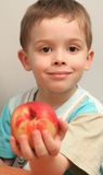 El muchacho sostiene un melocotón Imagenes de archivo