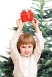 El muchacho sostiene un regalo del Año Nuevo sobre la cabeza Imagen de archivo libre de regalías