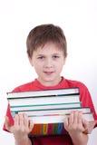 El muchacho sostiene una pila de libros Imágenes de archivo libres de regalías