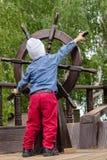El muchacho sostiene una rueda de madera del ` s de la nave Fotos de archivo