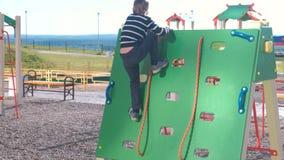 El muchacho sube en una pared que sube que lleva a cabo la cuerda en el patio metrajes