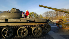 El muchacho sube la armadura de un tanque militar Fotografía de archivo
