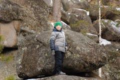 El muchacho subió sobre un canto rodado en el medio de las rocas imágenes de archivo libres de regalías