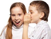 El muchacho susurra a la muchacha en el secreto del oído Foto de archivo
