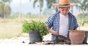 El muchacho tailandés asiático joven prepara el suelo negro a poca planta encendido en el jardín metrajes