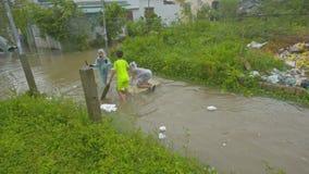 El muchacho tiene natación de la diversión en paseo de los amigos del tablón a lo largo de la calle inundada