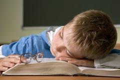 El muchacho tiene sueño caido en t imagen de archivo