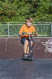 El muchacho tiene vespa del empuje del montar a caballo de la diversión en el parque del patín Imagen de archivo libre de regalías
