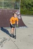 El muchacho tiene vespa del empuje del montar a caballo de la diversión en el parque del patín Foto de archivo libre de regalías