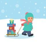 El muchacho tira de un trineo con los regalos Imagen de archivo
