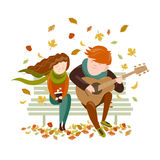 El muchacho toca la guitarra para una muchacha en el parque del otoño Imagen de archivo
