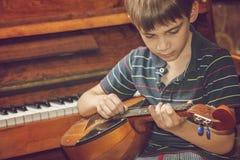 El muchacho toca la guitarra y toma los acordes, dombra en el fondo del piano Fotos de archivo libres de regalías