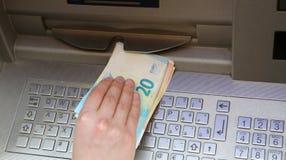 El muchacho toma el dinero en la máquina de la atmósfera en ciudad europea Imagenes de archivo